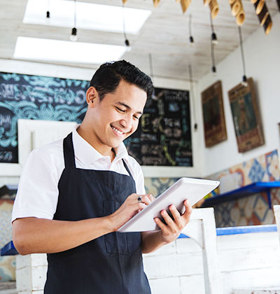 Restaurant owner looks at commercial mortgage application form while at work