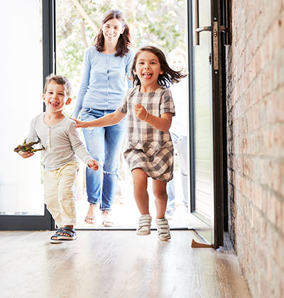 Happy children running into their new house with mother and father walking in smiling behind them