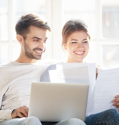 Smiling couple review papers and laptop for consolidation options