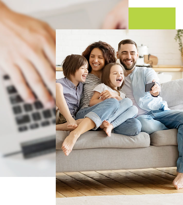 Young family gathered together on couch in their home as they watch a funny video