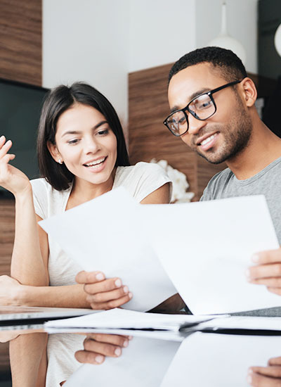 female on left and male on right look at papers will using the mortgage calculator