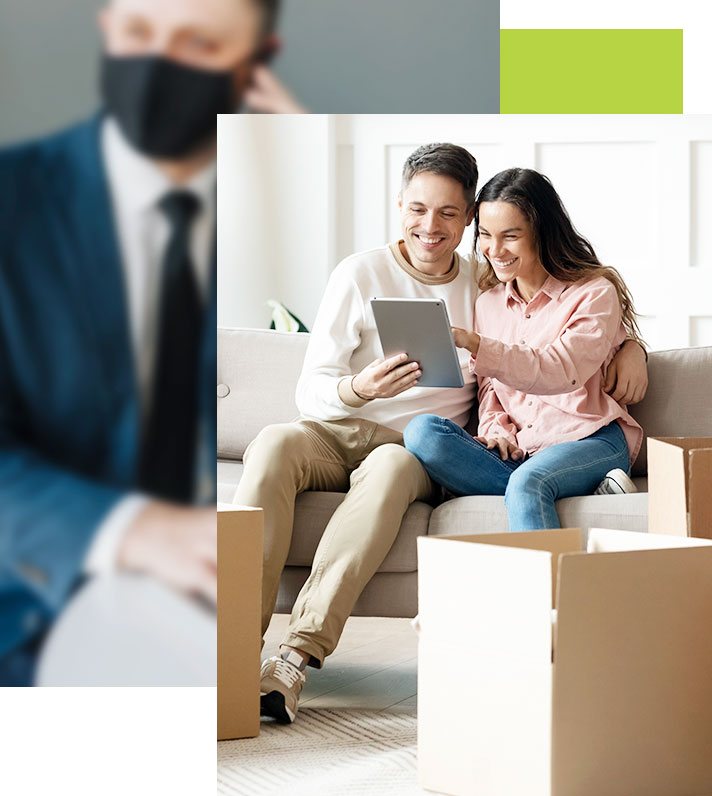 Young couple are new homeowners. Looking at iPad with moving boxes around them