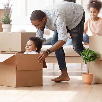 Happy father pushes his children around in moving boxes